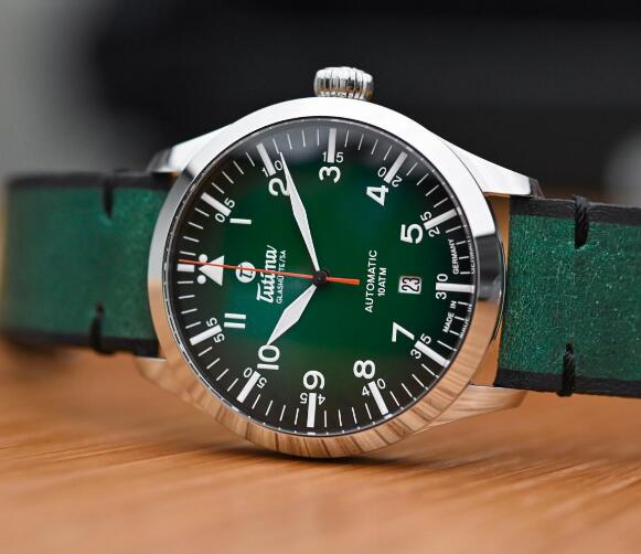 The orange second hand is striking to the green dial.